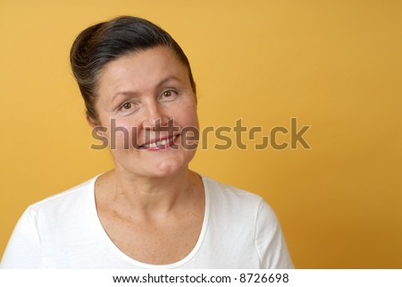 Happy, smiling older woman on bright yellow background