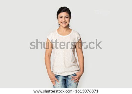 Happy smiling pleasant indian millennial confident woman wearing white mock up t-shirt for design advertising with copy space for promotional text looking at camera isolated on grey studio background