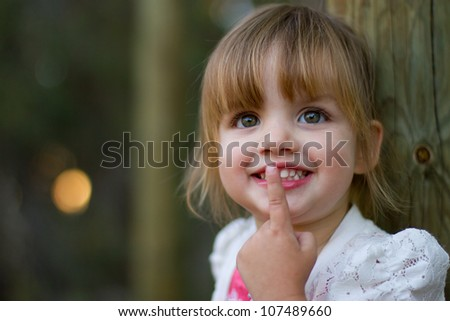 Happy smiling portrait of a 2 year old girl leaning against a wooden post with finger over lips