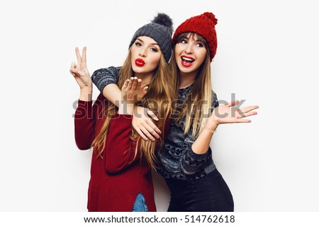 Happy smiling pretty friends hugging and showing peace hand sign on white background. Cute cheerful women in stylish   knitted  hat and sweaters having fun, laughing, hugging.  #514762618