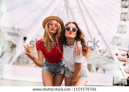 happy smiling pretty girls having fun.stylishly dressed in short denim shorts and bright t-shirts, sunglasses