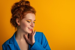 Happy smiling redhead freckled woman with colorful bold eyes makeup posing on orange background. Copy, empty space for text