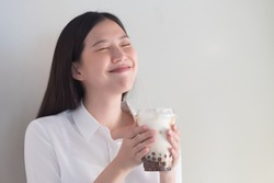 Happy smiling refreshing asian woman drinking iced bubble milk tea; aka boba tea, pearl milk tea, tapioca tea; Asian exotic beverage concept