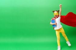 happy smiling schoolgirl in a red cape and a superhero mask and with a school book in her hands,runs and jumps on the green background of the studio. The child is ready for successful learning
