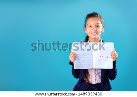 Happy smiling schoolgirl in uniform holding and showing notebook with excellent results of test or exam on blue background Stock photo ©