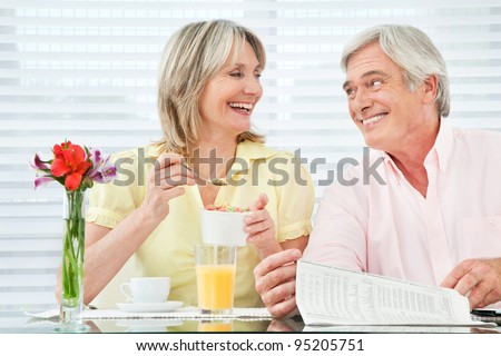 Happy smiling senior couple eating breakfast at home