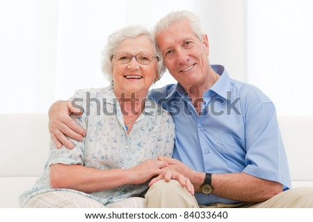 Happy smiling senior couple embracing together at home