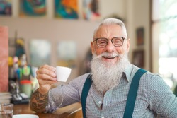 Happy smiling senior man drinking coffee in bar restaurant - Hipster trendy older male portrait - Lifestyle people concept