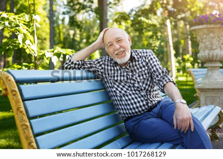 Happy smiling senior man outdoors. Elderly man in casual sitting on the bench in the park, copy space