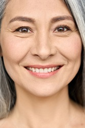 Happy smiling senior older middle aged Asian woman with grey hair and radiant face with perfect skin. Advertising of radiant foundation skincare and makeup for natural glow and healthy skin.