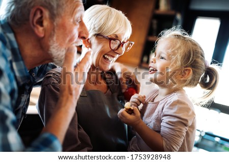 Happy smiling senior randparents playing with their granddaughter Сток-фото ©