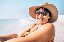 Happy smiling senior woman in sunglasses and big hat taking sun bath on the seaside portrait