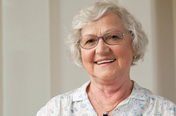 Happy smiling senior woman looking at camera at home