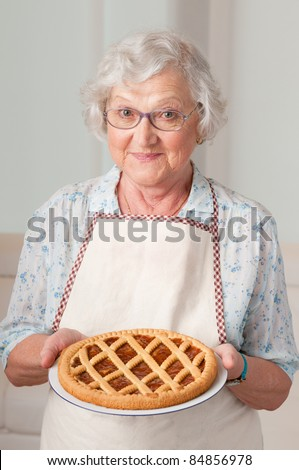 Happy smiling senior woman showing her apricot tart - stock photo
