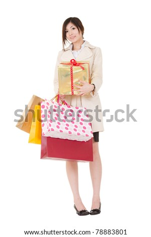 Happy smiling shopping woman holding bags and gift box and looking at you, full length portrait isolated on white background.