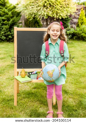 Happy smiling six years old blond caucasian child girl standing outdoor in front of the chalkboard - back to school, education concept.