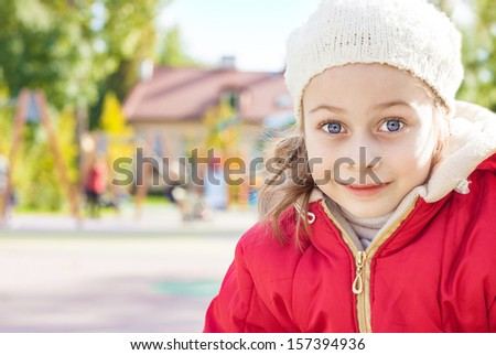 Happy smiling small five years old caucasian girl in warm clothes - close up autumn outdoor portrait with playground in background - careless childhood