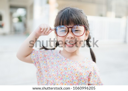Happy smiling smart and nerd little asian girl in glasses and pointing finger at brain and going to school for the first time.Child with school kindergarten.Child development and Education concept. #1060996205