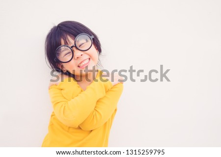 Happy smiling smart and nerd little asian girl in glasses.Portrait confident smiling little girl holding hugging herself isolated white wall background.Positive human emotion, attitude, Love yourself.