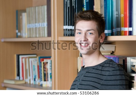 Happy smiling student in a college library looking at camera - stock photo