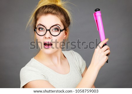 Happy smiling student looking woman wearing eyeglasses holding big oversized pencil having perfect idea or problem solution. #1058759003