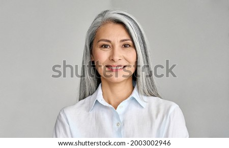 Happy smiling stylish confident 50 years old Asian female professional standing looking at camera at gray background. Portrait of sophisticated grey hair woman advertising products and services.