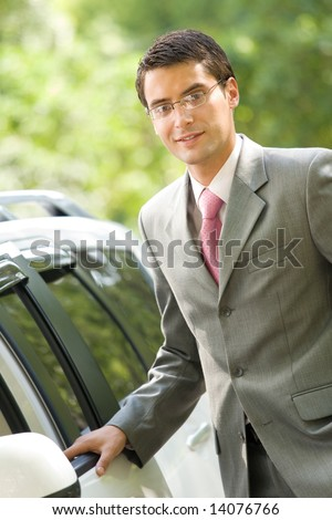 Happy smiling successful businessman standing near new car, outdoors
