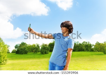 Happy smiling teen boy taking a picture of himself with camera on the cell phone in the park on sunny summer day