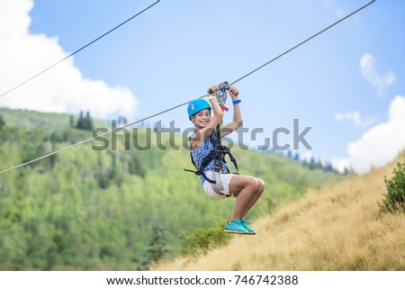 Happy smiling teen girl riding a zip line ride while on family vacation #746742388