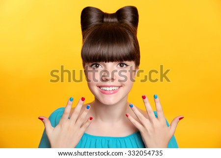 Happy smiling teen girl with bow hairstyle and colourful manicured polish nails. Funny girl showing ten fingers isolated on studio yellow background.