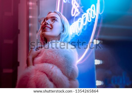 Happy smiling teen hipster girl in stylish glasses and fur looking up dreaming standing  near neon sign on street, female teenager fashion model woman in city night light glow, back to 80s