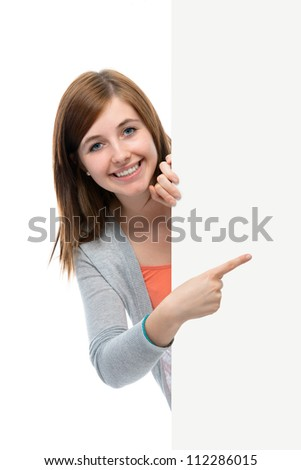 happy smiling teenage girl points her finger at a blank board