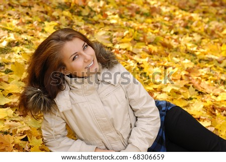 Happy smiling teenager girl lying in autumn park