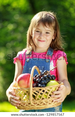Happy smiling three  child holding a fruit basket