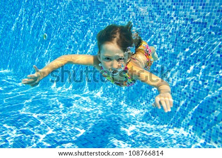 Happy smiling underwater child in swimming pool, beautiful girl swims and having fun. Kids sport on summer vacation. Active holiday