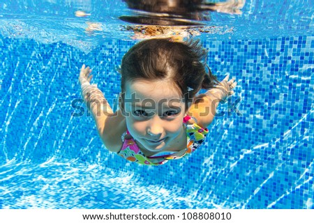 Happy smiling underwater child in swimming pool beautiful girl swims and having fun Kids sport on family summer vacation Active holiday