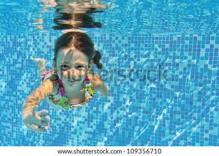 Happy smiling underwater child in swimming pool, beautiful girl swims and having fun. Kids sport on family summer vacation. Active healthy holiday - stock photo