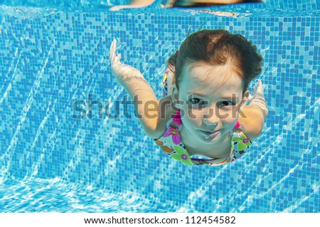 Happy smiling underwater child in swimming pool, beautiful girl swims and having fun. Kids sport on family summer vacation. Active healthy holiday