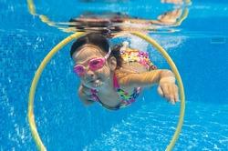 Happy smiling underwater child in swimming pool. Little girl swims. Kids sport
