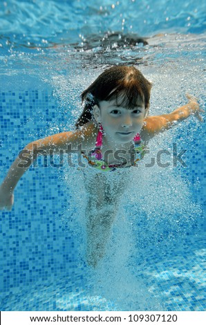 Happy smiling underwater child jumps to swimming pool beautiful