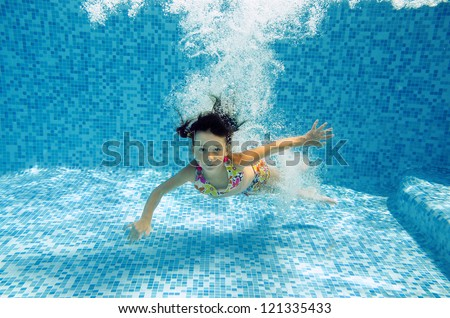 Happy smiling underwater child jumps to swimming pool, beautiful little girl swims and having fun. Kids sport on family summer vacation. Active healthy holiday