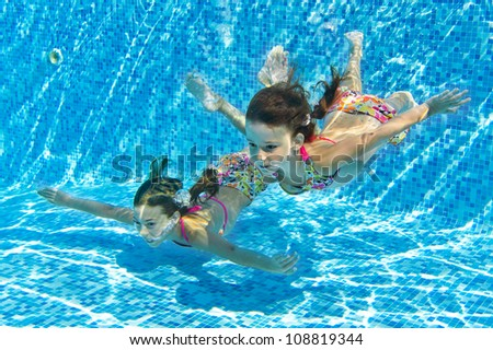 Happy smiling underwater children in swimming pool, beautiful girls swim and having fun. Kids sport on family summer vacation. Active holiday