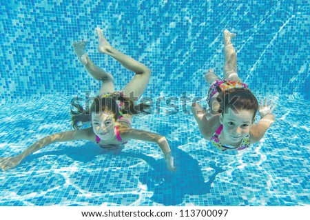 Happy smiling underwater children in swimming pool, beautiful healthy girls swim and having fun. Kids sport on family summer vacation. Active holiday