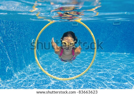 Happy smiling underwater kid in swimming pool