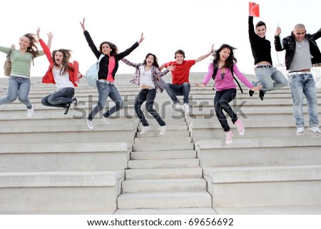 HAPPY,SMILING UNIVERSITY KIDS JUMPING ON CAMPUS