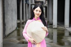 Happy smiling Vietnamese girl; portrait of exotic asian Vietnam woman in traditional Vietnamese Ao Dai dress