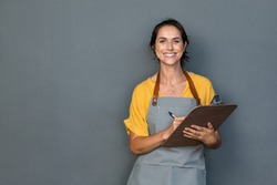 Happy smiling waitress ready to take customer order while looking at camera isolated on grey wall. Mature woman wearing apron while writing on clipboard standing against gray background and copy space