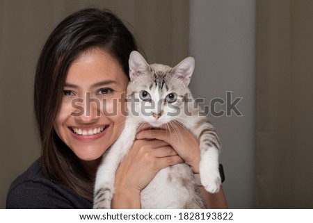 Happy smiling woman and her white striped cat with looking at the camera posing for a picture
