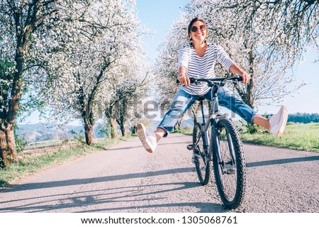 Happy smiling woman cheerfully spreads legs on bicycle on the country road under blossom trees. Spring is comming concept image.