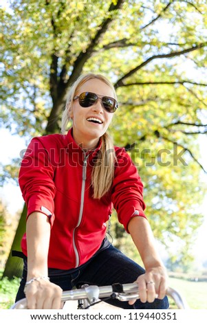 Happy smiling woman cycling on bicycle, autumn or summer park exercising, commuting
